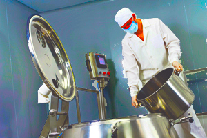 Manufacturing Worker Loading Lanolin into a Stainless Steel Vessel Used to Make Skin Care Producs
