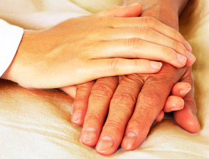 Woman Holding an Elderly Man's Hands in a Comforting Way