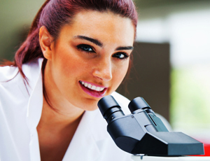 Microscopist in Lanolin Skin Laboratory Looking Up From Her Work Smiling